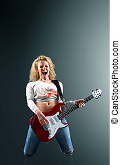 beautiful blonde woman with a guitar sings a rock song