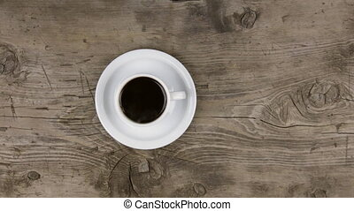 Zoom of hot steaming cup of coffee standing on a wooden table.