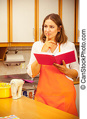 Housewife with cookbook in kitchen. - Mature thoughtful...