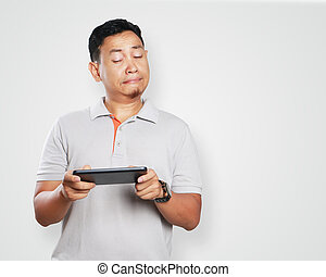 Funny Young Asian Guy Playing Games on Tablet - Photo image...