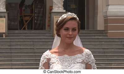 Closeup Bride in Long Dress Stands at Opera Theatre Entrance...