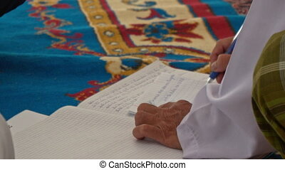 Man Writes in Wedding Register Book on Carpet - man in white...