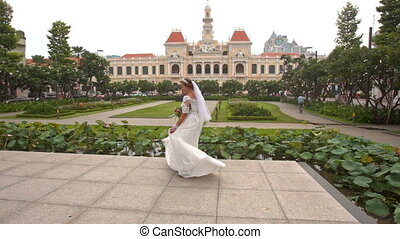 Bride in Long Turns around on Square in Saigon in Vietnam -...
