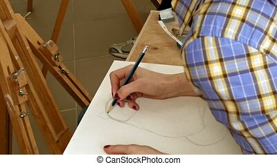 Female artist draws a pencil sketch in art studio - Female...