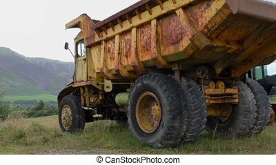 Old rusty dump truck close up - Big old rusted yellow brown...