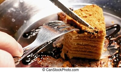 Cake being cut with fork and knife. Close up shot. - Piece...
