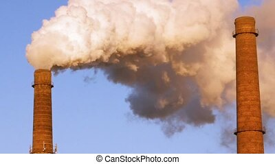 Factory plant smoke stack over blue sky background. Energy...