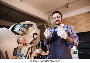 Carpenter working on an electric buzz saw cutting some...