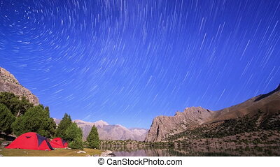 Moon lights the mountains. TimeLapse. Traces of stars...