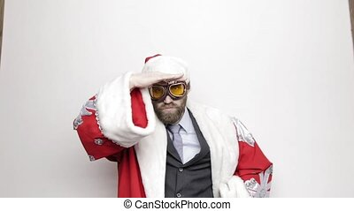 businessman in a suit of Santa Claus raised hand to his eyes and looks into the distance