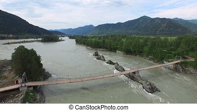 Bridge over Katun river in flood. Altay, Russia