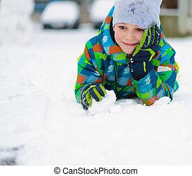 Children throwing snowballs in snowy winter park