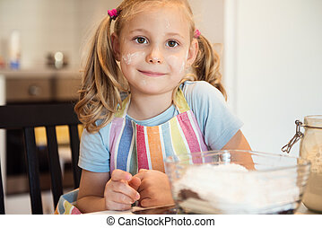 Portrait of pretty little girl preparing Christmas sweets in...