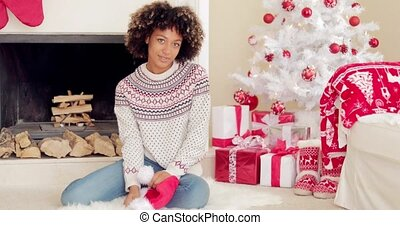 Smiling young woman holding a Santa hat as she relaxes on...