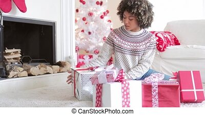 Surprised woman holding a large Christmas gift - Surprised...