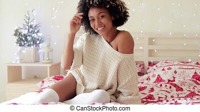 Cute young woman with a sweet smile relaxing on her bed in a...