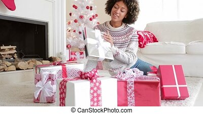 Smiling young woman opening her gifts at Christmas sitting...