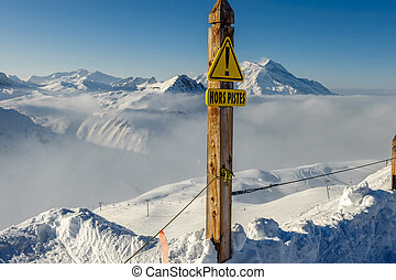 Off-piste sign at mountains in clouds with snow in winter -...