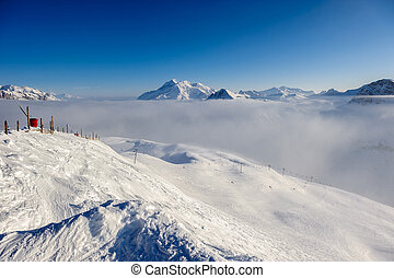 Mountains in low clouds with snow in winter - Alpine winter...