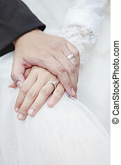 hand of groom and bride warming holding with wedding daimond...
