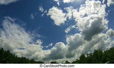 Clouds In The Sky Moving Above The Trees. Time lapse -...