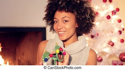 Fun vivacious young woman celebrating Christmas wearing a...
