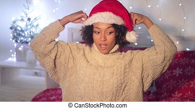 Young woman watching the pompom on a Santa hat - Young woman...