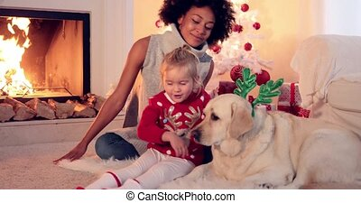 Family Christmas celebration next to fireplace with a young...