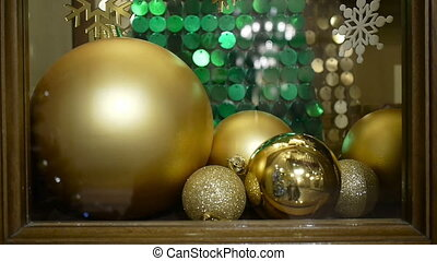 Close-up New Year's and Christmas decorations in window. Gold balls.