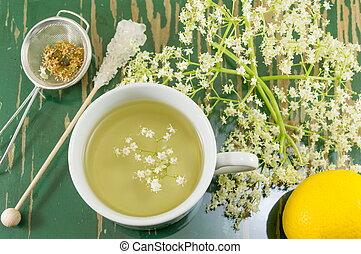 Elder tea in white cup and elder flowers