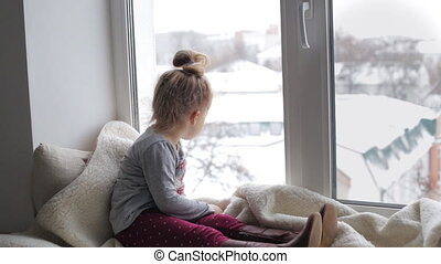 Young girl on a window sill - Young girl sitting on a window...