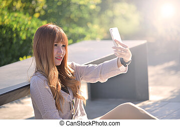 Happy beatuiful asian waman with smartphone sit in garden. -...