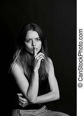 The girl with long hair holds finger near the lips . gesture...