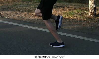 Sportsman running along the road. Athletic legs. Slow motion...