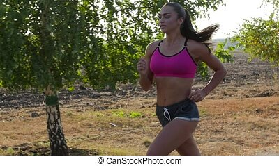 Morning jogging beautiful girl on a country road. Slow motion