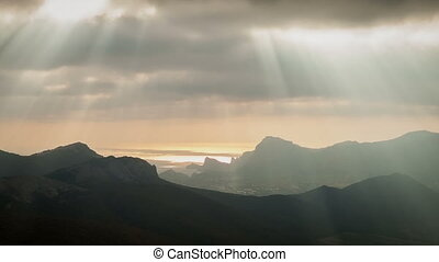 Sun rays through the clouds floating over the mountains and...