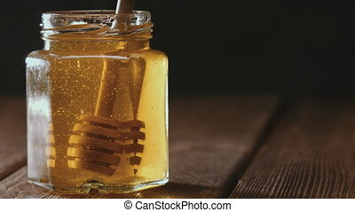 Close up of honey stick in jar