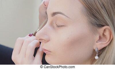 Make up artist putting on mascara on model's eyes. Eye make...