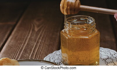 Wooden honey stick watering cheesecake - Closeup view of a...