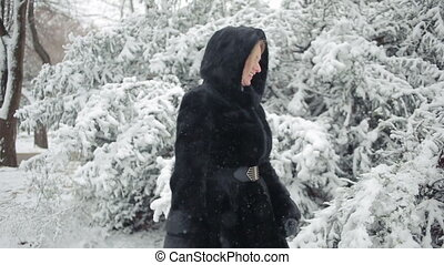 Young beautiful woman in stylish mink coat on a background of a winter park