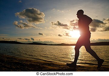 Training at sunset.Running tall man.  A silhouette of jogger at path along lake coastline.
