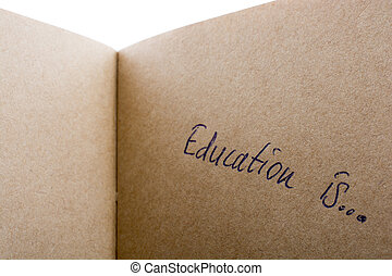 Writing on a notebook - 'Education is...' written on a...