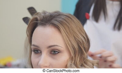 Hairdresser combing hair of female client in hair salon.