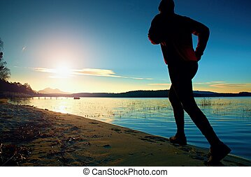Sportsman running at amazing summer sunset along coastline...