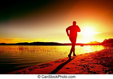 Sportsman running at amazing summer sunset along coastline...