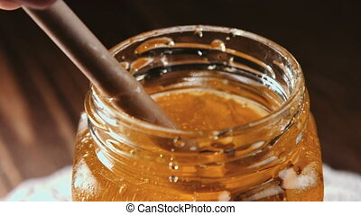 Honey stick getting out of jar - Close up view of glass jar...