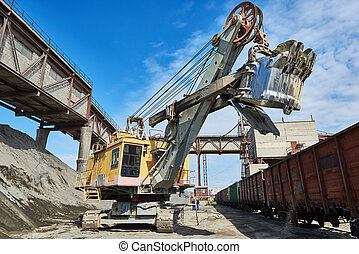 heavy excavator loading gravel into train for rail...