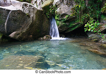 Small beautiful waterfall among the rocks in mountain forest...