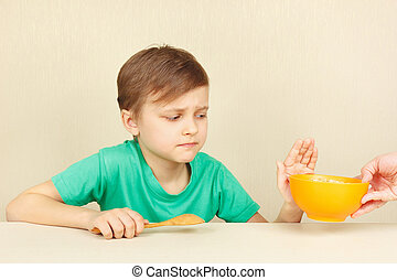 Little disaffected boy refuses to eat cereal