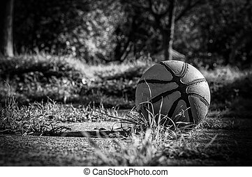 Old basketball in country playground in black and white